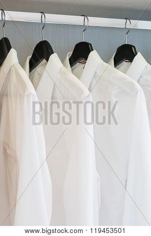White Shirts Hanging On Rail