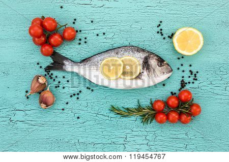 Raw Dorado Fish With Garlic, Lemon And Tomatoes. Top View, Copy Space