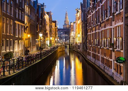 AMSTERDAM NETHERLANDS - 17TH FEBRUARY 2016: A view along Oudezijds Kolk canal in Amsterdam at night. Buildings bikes and the top of The Oude Church can be seen.