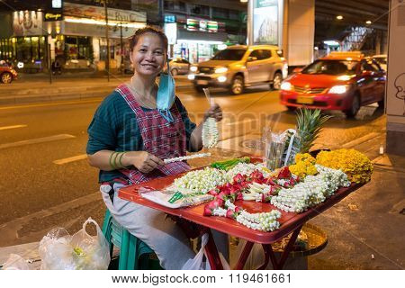 BANGKOK, THAILAND, JANUARY 15, 2016 : A woman is selling religious offerings of marigold, jasmin and rose flowers for the early morning Buddhist monk's alms in the Sukhumvit road in Bangkok, Thailand