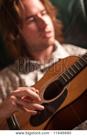 Young Musician Plays His Acoustic Guitar under Dramatic Lighting.