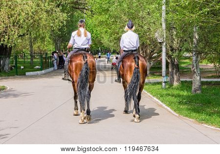 Female Mounted Police On Horse Back In The City Park
