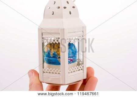 Hand Holding A Cage With A Globe In It