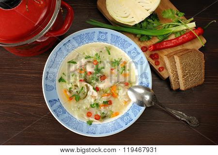 Cabbage Soup With Chicken In Blue Plate Served With Rye Bread, Chilli, Fresh Onion And Cabbage