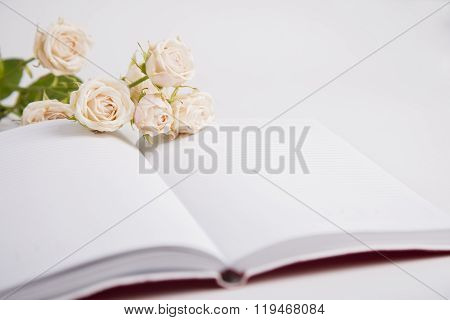 Bouquet Of Creamy Roses Lying On Open Notebook