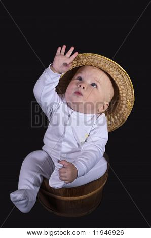 The Baby In The Hat Sits In A Wooden Bucket