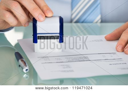 Person's Hand Pressing Stamper On Document