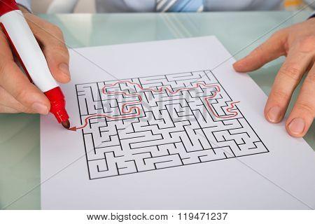 Person Hand Solving Maze Puzzle