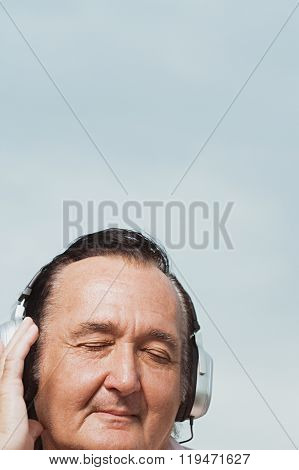 Senior man listening to headphones