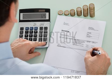 Businessperson Calculating Invoice With Coins At Desk
