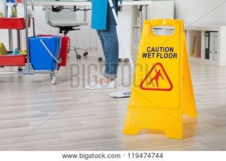 Female Janitor Mopping Wooden Floor With Caution Sign