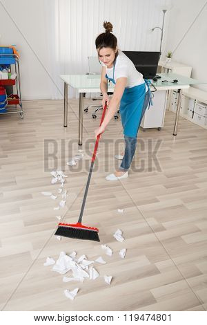 Female Janitor Sweeping Hardwood Floor