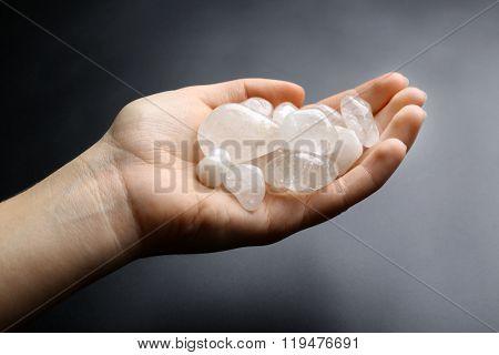 Woman holding semiprecious stones in her hand on dark grey background
