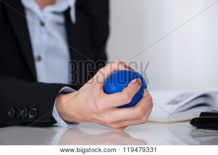 Businessperson Squeezing Stressball In Hand