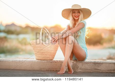 Bright blonde in beautiful hat in the rays of the setting sun