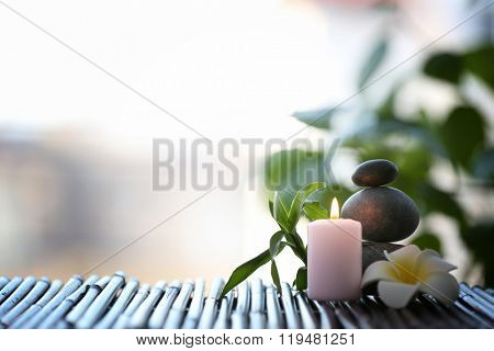 Spa stones with candle and tropical flower on blurred background