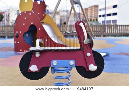 a view of a public urban playground with a spring rider in the foreground and a slide in the background