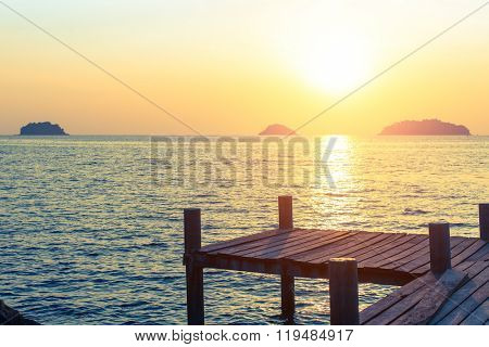 Wooden walkway on the sea coast during sunset.