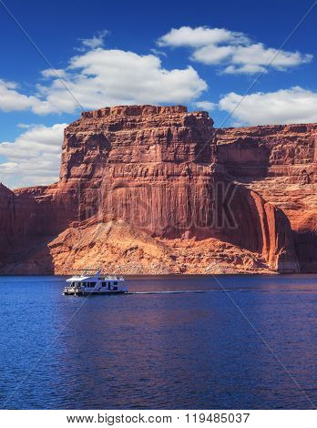 Scenic huge artificial water basin of the Colorado River, USA. Lake Powell is surrounded by magnificent sandstone hills. Walk on white boat on a sunny day