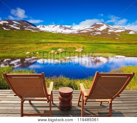 In the smooth water of lake reflects cold cloudy sky. At the lake on wooden platform there are two deckchairs