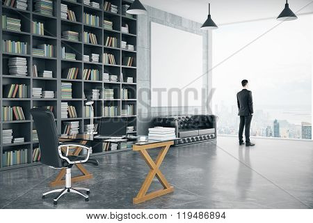 Businessman In Modern Personal Office With Big Bookcase, Sofa, Glassy Table And Blank Poster, Mock U