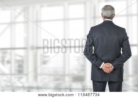 Portrait of smiling senior businessman standing looking out of office window with his hand behind his back.