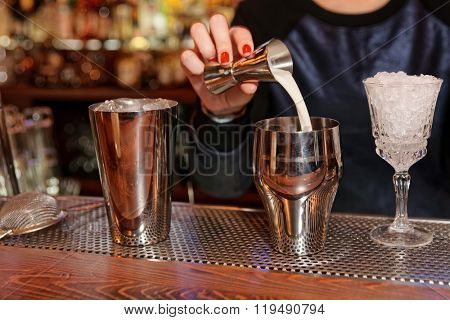 Bartender is adding milk to the metal shaker