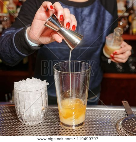 Female bartender is adding an ingredient to the glass