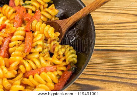 Italian Pasta Fusilli With Tomato Sauce And Sausage In Pan, Wooden Spoon On Table, Space For Text