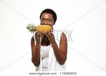 Hungry excited african american young woman holding and biting fresh pineapple over white background
