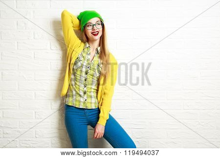 Happy Hipster Girl at White Brick Wall Background