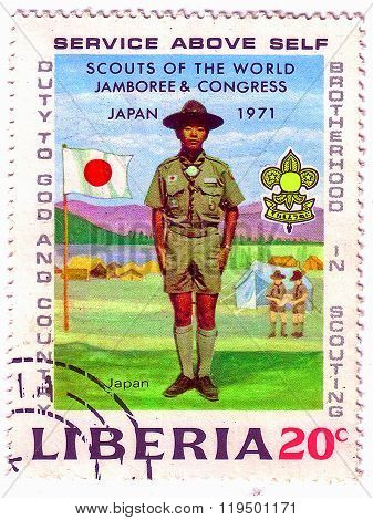 Liberia - Circa 1971: Stamp Printed By Liberia, Shows Boy Scout, Emblem And Flag Of Japan, Circa 197