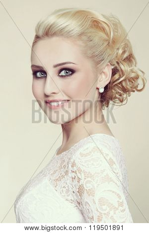 Vintage style portrait of young beautiful happy smiling blonde bride with stylish prom hairdo
