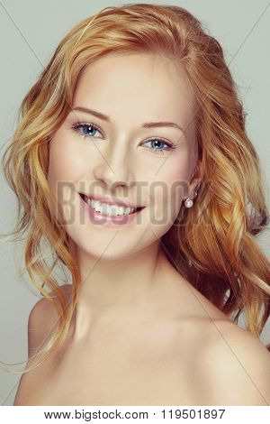 Portrait of young beautiful happy smiling girl with curly red hair and clean make-up