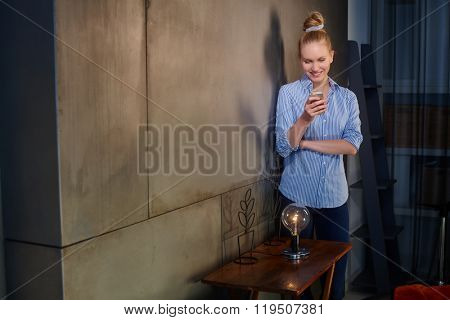 Happy blonde woman standing by wall at home, reading text message, holding mobilephone, smiling.