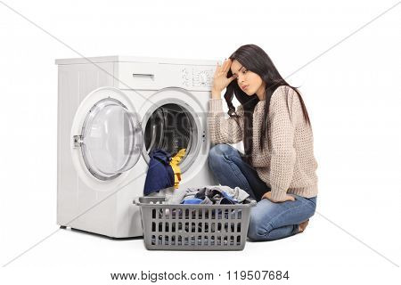 Sad woman emptying a washing machine seated on the floor isolated on white background