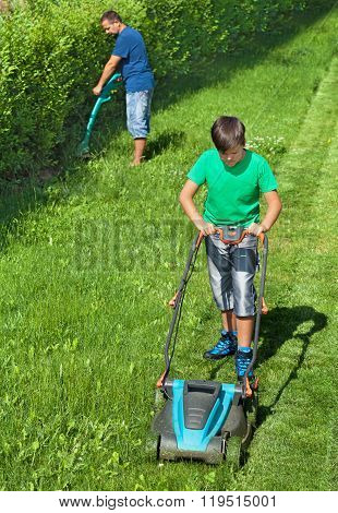 Boy Mowing The Lawn With Man Trimming At The Edges