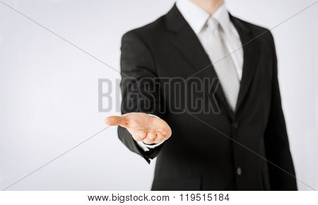 people, business, technology and advertisement concept - close up of man hand showing something on empty palm