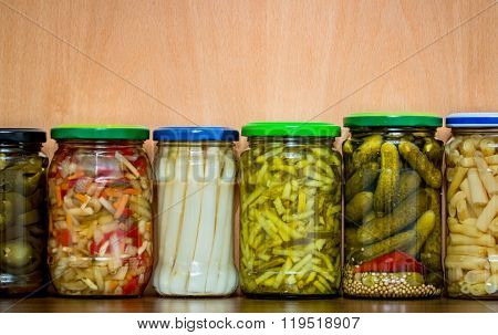 Jars of different pickles against wooden background