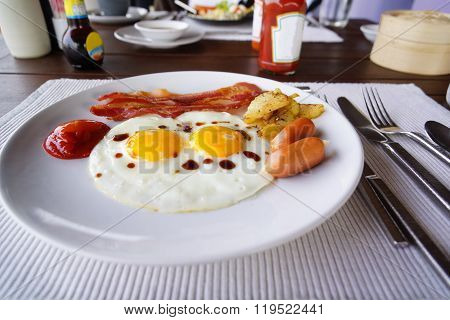 English breakfast with fried eggs bacon sausages