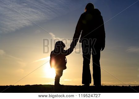 mother and little daughter travel at sunset