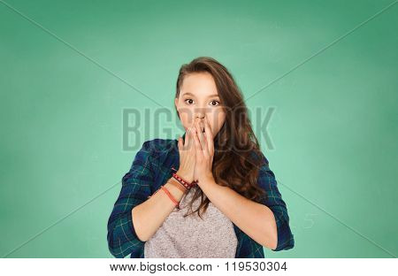 people, school, education, emotion and expression concept - scared teenage student girl over green chalk board background