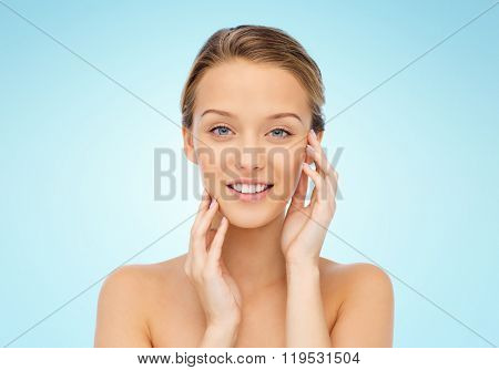 beauty, people and health concept - smiling young woman with bare shoulders touching her face over blue background