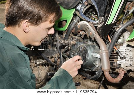 Teenage Boy Working On A Motorbike