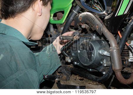 Teenage Boy Working On A MotorBike Enginge