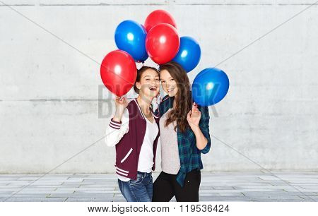 people, friends, teens, holidays and party concept - happy smiling pretty teenage girls with helium balloons over gray stone wall background