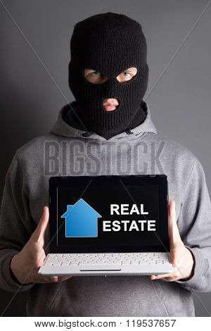Home Safety Concept -masked Man Holding Computer With Real Estate Site