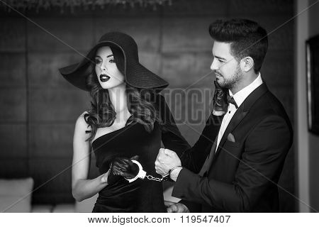 Woman In Hat Holding Man On Handcuffs Black And White