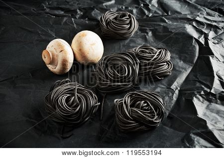 Five Servings Of Black Pasta With Cuttlefish Ink And Two Mushroom On A Dark Background. Horizontal