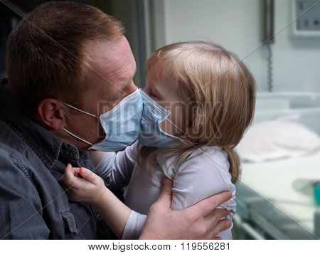 Hospital ward. Father kissing daughter through medical mask. Little daughter
